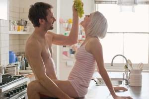 Man feeding woman grapes as foreplay