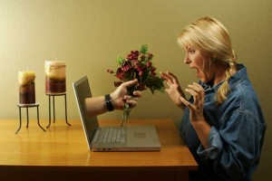 Woman getting flowers from laptop