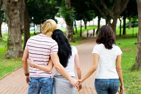 Threesome walking down a path in the park