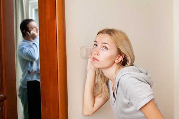 Jealous woman listening to husband in secret