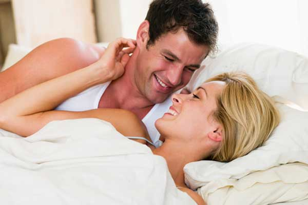 Man and woman affectionate love making in bed