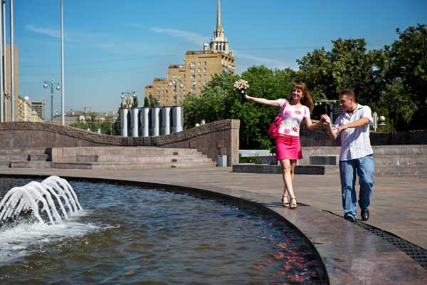 Man and woman walking along water fountain